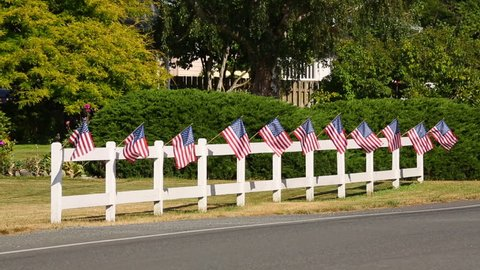 American car pickup truck suv passing patriotic display of American flags waving on white picket fence. Fourth of July 4th Independence Day decorations in rural small town USA HD video.