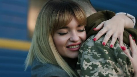 Romantic reunion. Close up view of beautiful young woman feeling happy while hugging embracing her soldier boyfriend. Turning back home, homecoming, welcomed by wife. happiness