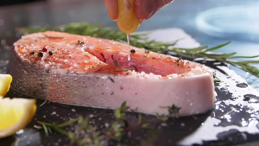 Slow motion close up view of unrecognizable hand squeezing lemon juice on salmon's fillet. A chef's hand squeezes a fresh lime over a peace of sea fish. Mackerel in a marinade with spices