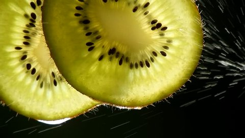 Close up a slice of kiwi, a drop of water falling.freshness concept,juices and kiwi