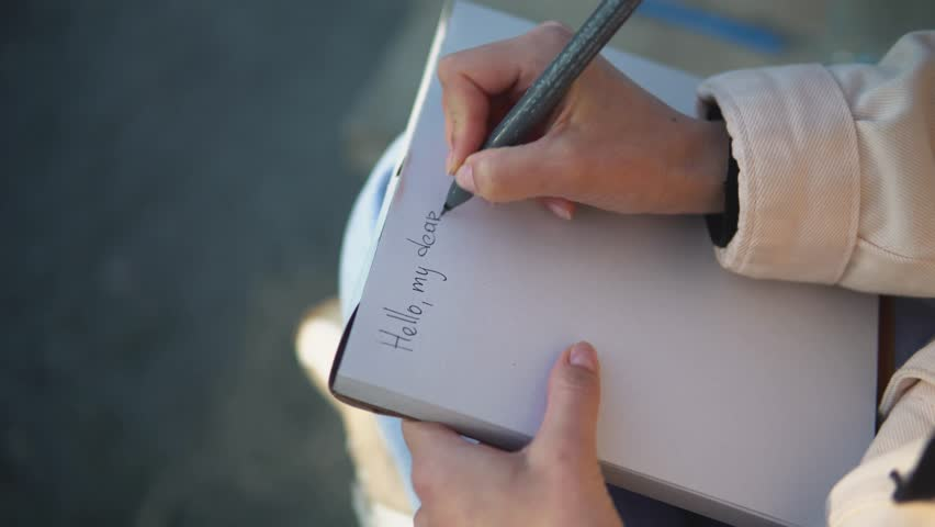 The girl writes a letter to her pen friend on a white notepad | Shutterstock HD Video #1028855090