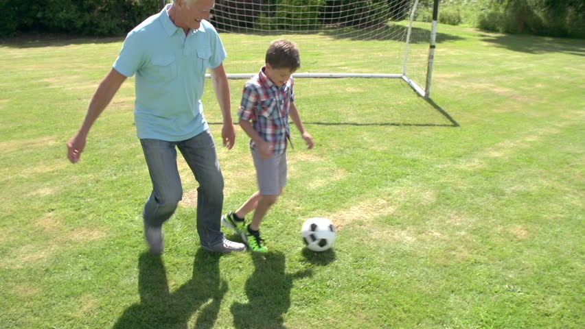 Grandfather and grandson playing football in summer garden. Shot on Sony FS700 at frame rate of 25fps