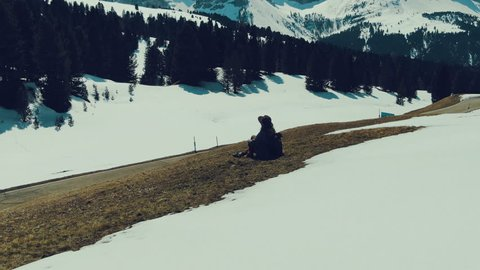 Aerial photography of girl traveler, who sits on mountainside and admires view of snow-capped mountains and forest on sunny day. Flight of camera over girl with transfer of perspective of mountains.