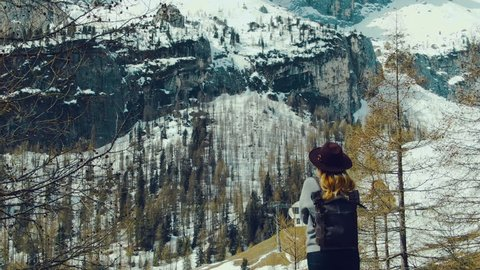Aerial photography of girl traveler, who stands on mountainside and admires view of snow-capped mountains and forest on sunny day. Flight of camera over girl with transfer of perspective of mountains.