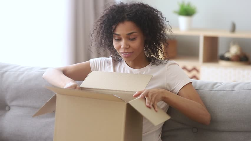 Happy african woman customer open cardboard box sitting on sofa at home, excited black girl consumer unpack big carton parcel looking inside receive surprising good purchase postal shipping delivery