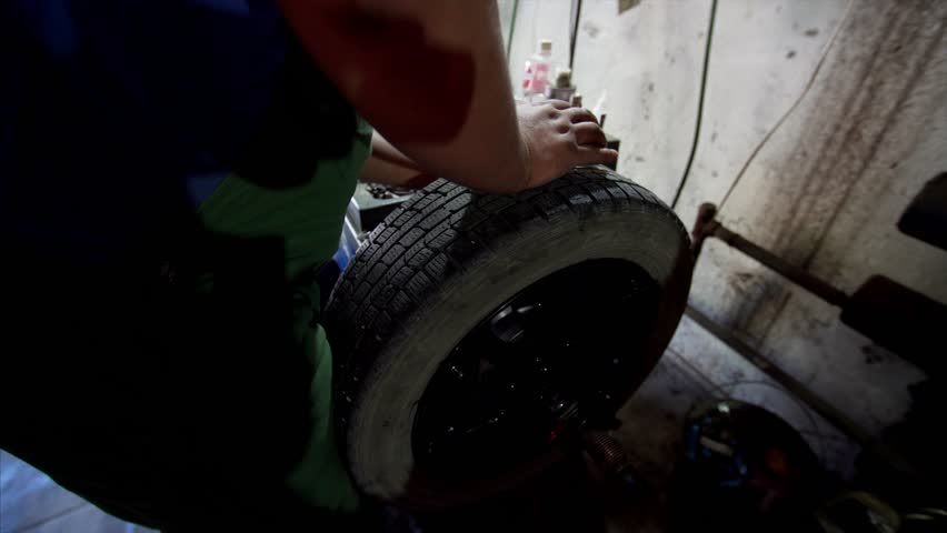 VLADIVOSTOK, RUSSIA – SEPTEMBER, 6, 2018: The close up shooting of a car mechanic checking the strength of the tire landing on an alloy tyre. | Shutterstock HD Video #1028953880