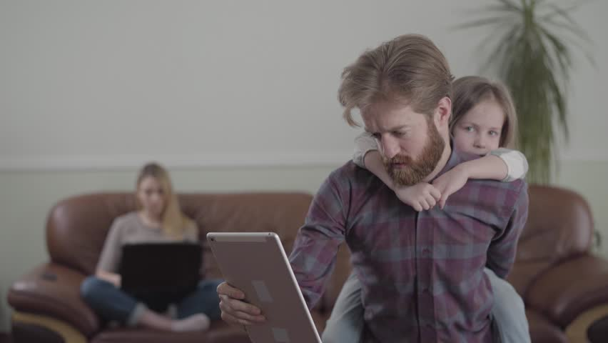 The bearded man working with tablet, involved in his job close up. Little sad girl sits on fathers back, trying to get attention. The mother on the sofa with laptop on the background | Shutterstock HD Video #1029001970