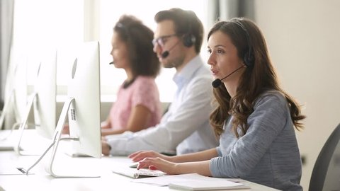 Young woman customer care support service agent call center operator in wireless headset talk consult online client using computer solving complaints on helpline or sell services in telesales office
