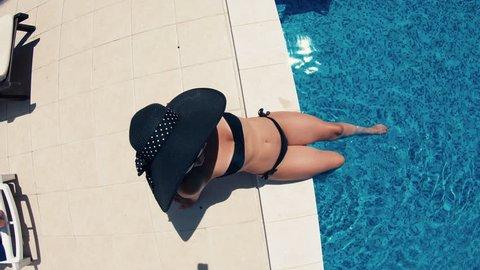 Beautiful, sexy woman in bikini sunbathing and relaxing by the pool