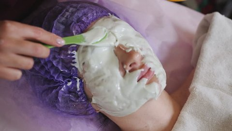 Beautiful woman with facial mask at beauty salon. Cosmetologist applying green facial mask to the face. Skin procedures cleaning cosmetology,