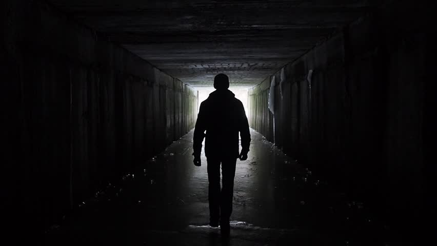 Man silhouette walking in a dark tunnel. Underground, post apocaloptic view. Exit concept.  | Shutterstock HD Video #1029169520