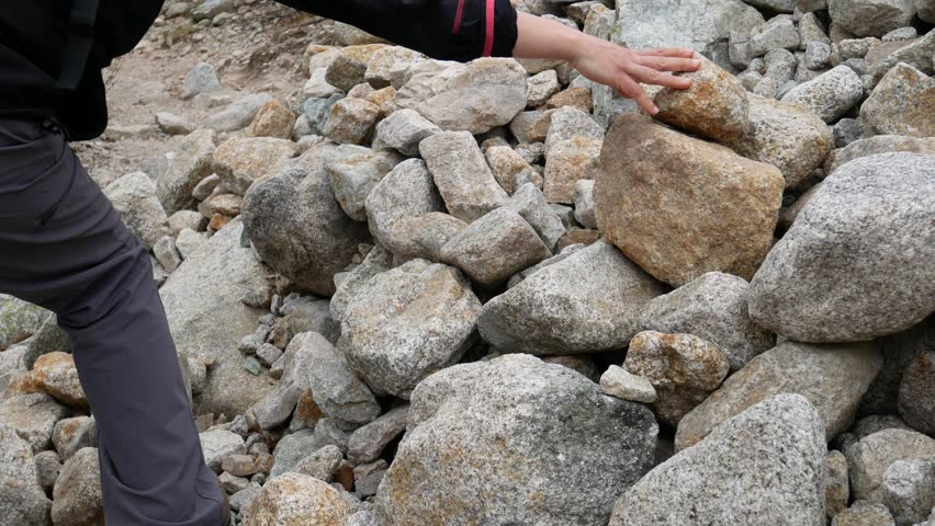 Hikers lay stones on a cairn, a man-made pile (or stack) of stones. Cairns are used as trail markers for mountain paths. Restonica Valley, Lac de Melo, Corse, France | Shutterstock HD Video #1029177890