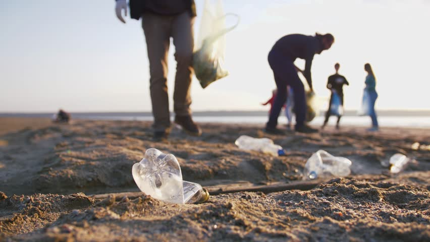 Close up shot of young man picking up plastic bottles on the beach, slow motion | Shutterstock HD Video #1029188840