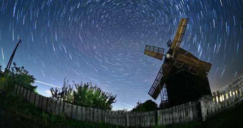 Timelapse of moving star trails in night sky. Space Milky Way galaxy rotating over the old rural windmill range rotation in summer time with movement clouds -  travel in old Ukraine destination.