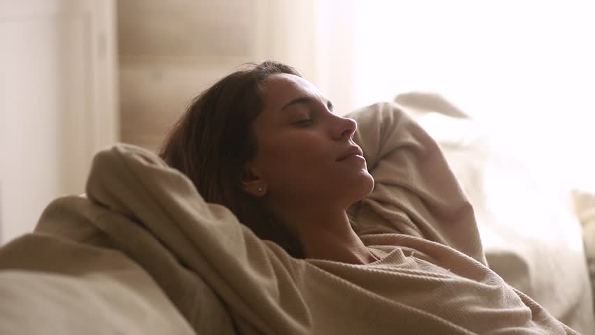 Calm young woman having healthy daytime nap dozing relaxing on couch with eyes closed hands behind head, peaceful girl sleeping breathing fresh air resting leaning on comfortable sofa at home | Shutterstock HD Video #1029331790