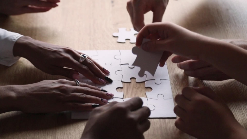 Side view hands of united diverse people taking part assembling white jigsaw puzzle, different ethnicity friends put pieces together search common solution, help support teamwork and synergy concept