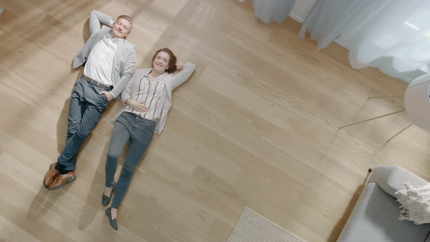 Young Couple are Lying on a Wooden Flooring in an Apartment. They are Happy, Smile and Laugh. Cozy Living Room with Modern Interior, Grey Sofa and Wooden Parquet. Top View Camera Footage. | Shutterstock HD Video #1029383870