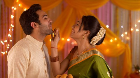a9791b60c7 Happy Indian nuclear family celebrating festival together - Young beautiful  wife feeding laddoo to husband.