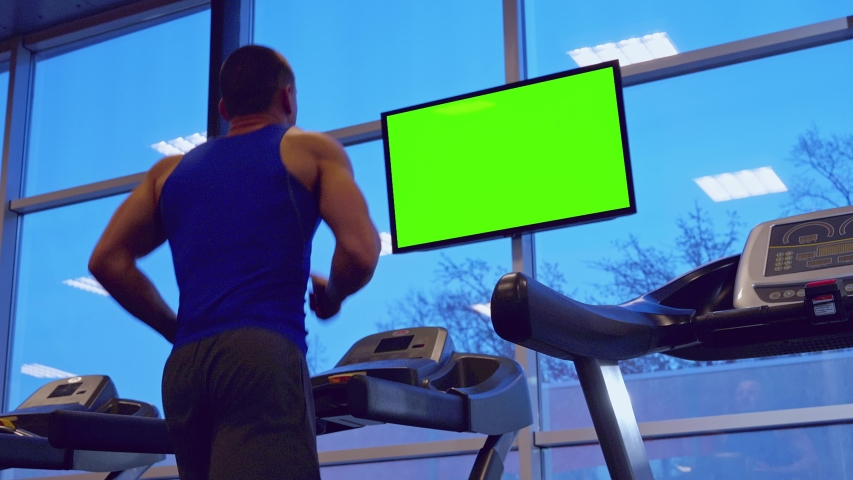 Strong athletic man running on a treadmill at a gym and watching a green screen