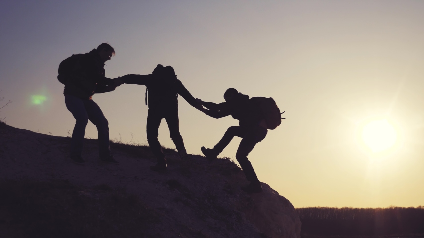 lifestyle teamwork help business travel silhouette concept. group of tourists lends a helping hand climb the cliffs mountains. people climbers climb to the top overcoming hardships the path to victory #1029418040