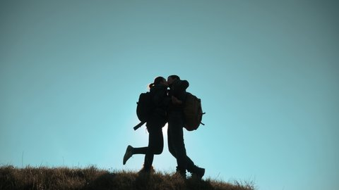 happy family teamwork friendship love romance business travel concept. couple of tourists man and woman with backpacks silhouette kissing on top of a mountain near a small dog. hikers couple kiss and