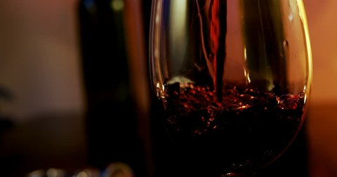 Close-up of red wine poured in wine glass. Bubbles in a glass.