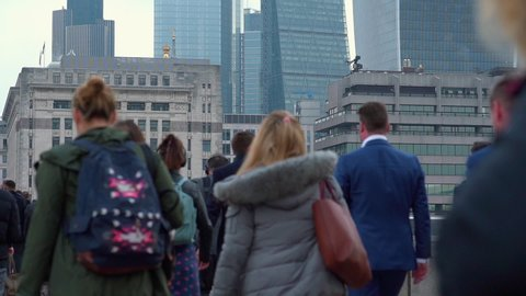 Crowd of pedestrian commuters crossing London Bridge on their way to work on cool morning in early May.  Slow motion version – real time version also available. Clip 26 of 66