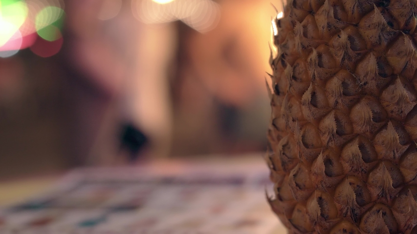 part of brown pineapple rind on table against blurred moving people and bright gleaming neon lights close view
