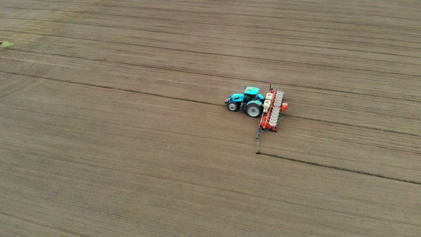 Aerial survey, spring, a tractor with special precision planters is working in the field, there is a planting of corn, or sunflower. planting season on the farm. modern technologies in agriculture.   Shutterstock HD Video #1029526430