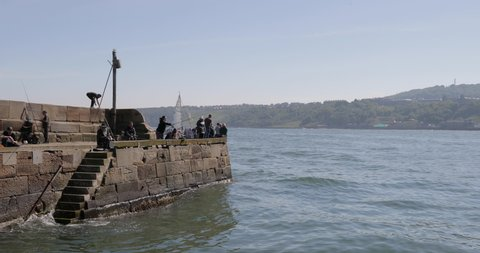 UNITED KINGDOM, SCARBOROUGH - MAY 2018: Fishing From Harbour Wall; Scarborough South Bay