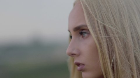 Cute blond woman at sunset in close up profile, on top of a mountain, looking at the sea in the late afternoon. Beauty shot golden hour 4K in slow motion.