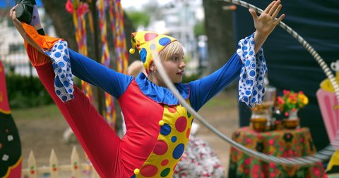 Young gymnast girl dressed as clown performs acrobatic dance with hula hupe hoop ring, 4K