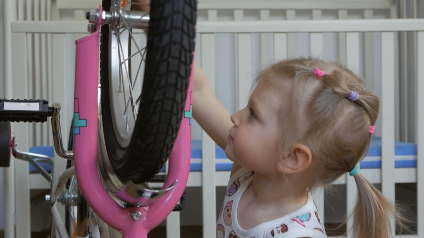 A little girl sitting in the children's room playing with the bike, turning the wheel. | Shutterstock HD Video #1029578090