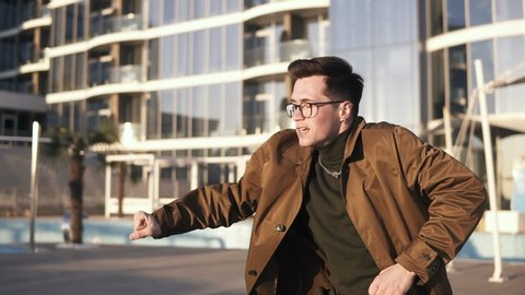 An attractive brunette young man in stylish glasses and gold necklace is performing modern freestyle dance outdoors on a bright, sunny day. Expression. Front view