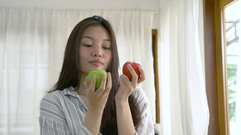 portrait of a young lovely pretty asian girl biting an green apple in white kitchen in morning. Her hands holding green and red apple that made her strong and healthy