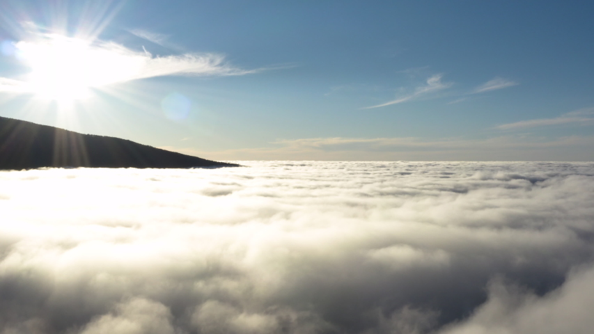 Aerial shot of a thick cloud layer during the golden hour, with the foot of a mountain in the background in Tenerife #1029661430