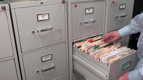 Office Temp Worker Looking Through File Cabinets for a File Folder.