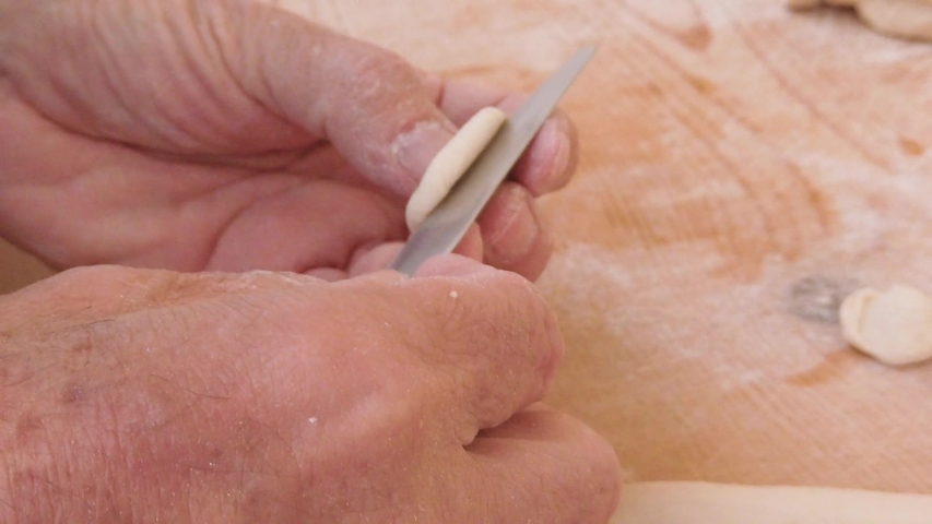 Hands of a man are making homemade pasta food on a wooden cutting board in the kitchen. | Shutterstock HD Video #1029709640