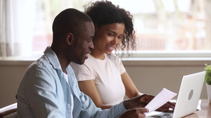 Happy african american young couple paying bank loan bills online at home, millennial black husband holding papers doing paperwork payment with wife using laptop planning budget sit at desk at home