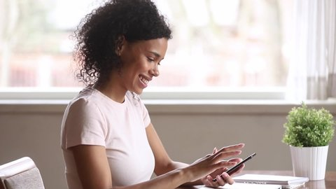 Smiling african american woman using smartphone dating app looking swiping on screen, happy mixed race young girl holding phone enjoy watching media in mobile online application on cellphone