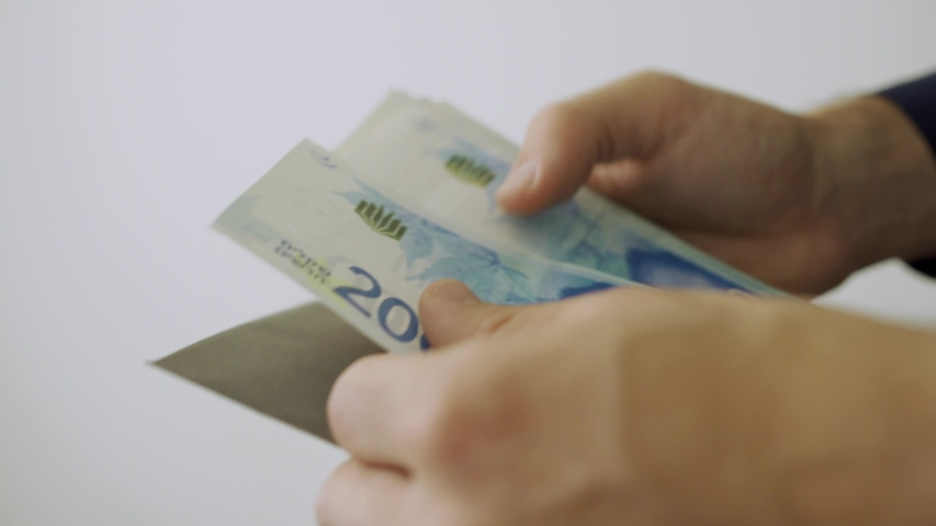 Hands take out Israeli money bills from black envelope and count it   Shutterstock HD Video #1029758090