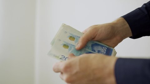 Slow motion of Israeli 200 shekel bills being counted by hand
