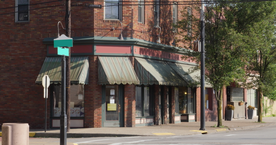 A summer establishing shot of a corner red brick bar or restaurant in a small town in Pennsylvania. Signage digitally removed for general stock usage. Pittsburgh suburbs. Winter version available. | Shutterstock HD Video #1029765500