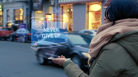 Unrecognizable woman standing on the street interacts HUD hologram with text Never give up. Girl in warm clothes uses technology of the future mobile screen on background of night city