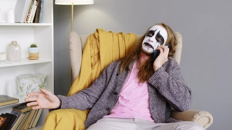 Male rock musician uses mobile phone and chatting. Web camera. Paint face. Strange man. Scary face.
