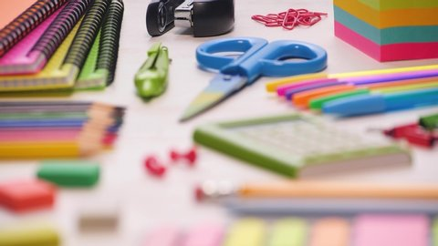 Shot of a school desk with different colorful supplies. Sliding focus. 4k.