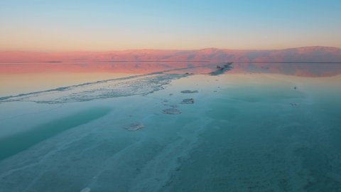 AERIAL, incredible view on the dead sea of an aqua color with beautiful red mountains in the background and a beautiful blue sky