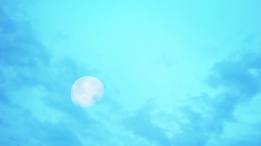 Moon in daylight On the bright sky and the black cloud moving fast