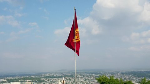 Flag of Kyrgyzstan waving in the wind with some clouds and blue sky. In the background the city of Osh can be seen.