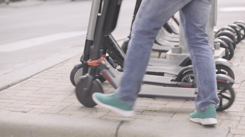 A man parks his electric scooter next to a row of other shared scooters | Shutterstock HD Video #1029992240